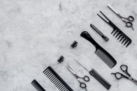 Combs and scissors on grey table background top view.