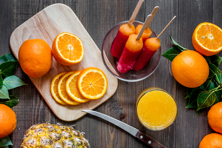 Orange juice, oranges, pineapple and citrus ice cream on wooden table background top view Banco de Imagens - 82659414