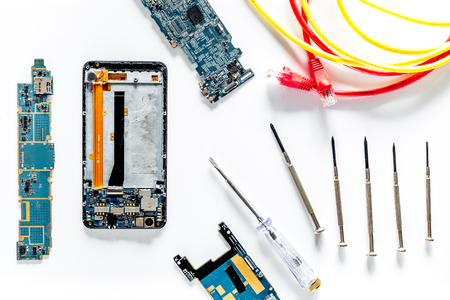 Parts of disassembled cell phone and screwdrivers on white background top view Stock Photo