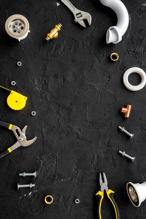 Plumber tools on black background top view copyspace