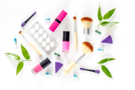 Contents of wonams beauty bag. Cosmetics, contraceptives and pills on white background top view