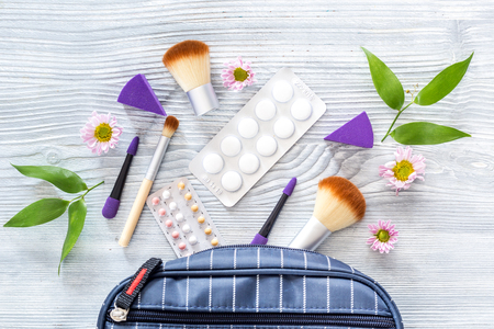 Contents of wonams beauty bag. Cosmetics, contraceptives and pills on wooden table background top view