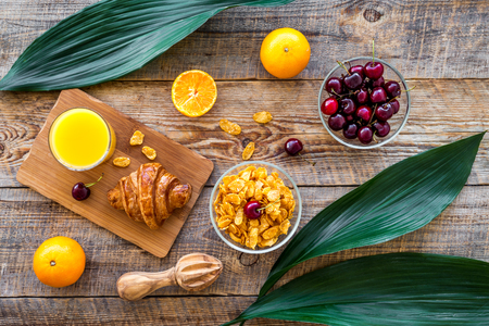 French breakfast. Fresh croissant, muesli, oranges, cherry on wooden table background top view