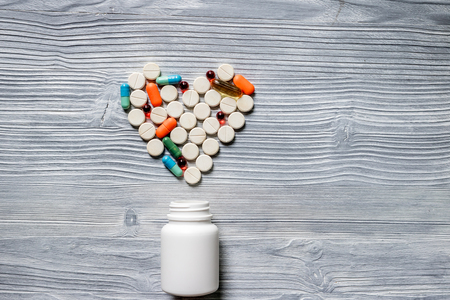 Heart made of pills and pill bottle on grey wooden table background top view copyspace Фото со стока