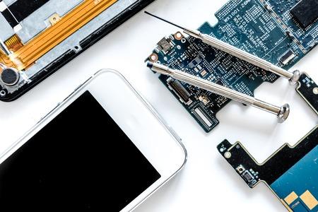 Teile des zerlegten Handys auf Draufsicht des weißen Hintergrundes