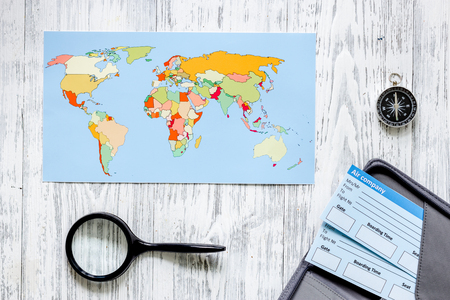 Search and buy tickets for travel. Tickets and world map on light wooden table background top view