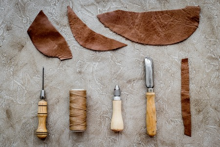 Set of leather craft tools on grey stone background top view mockup