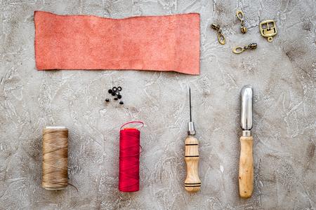 Set von Leder Handwerk Werkzeuge auf grauem Stein Hintergrund Draufsicht Mockup Standard-Bild - 82730024