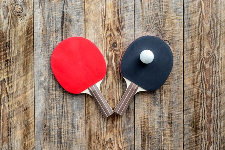 Sport background. Table tennis racket on wooden background top view copyspace