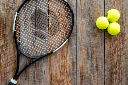 Sport background. Tennis balls and racket on wooden background top view copyspace