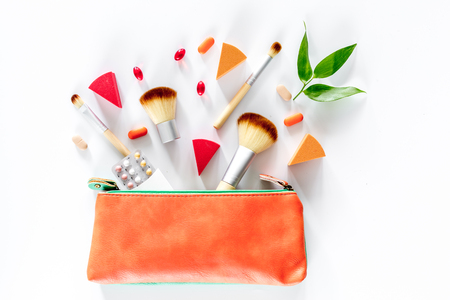 Beauty bag with cosmetics, contraceptives and pills on white table background top view copyspace