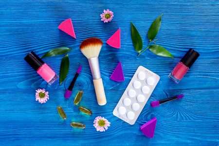 Contents of wonams beauty bag. Cosmetics and pills on blue table background top view copyspace