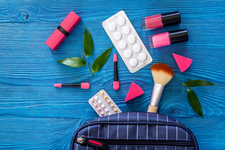 Cosmetic bag with contraceptives and pills on blue table background top view copyspace Stock Photo