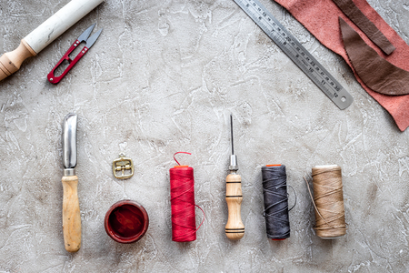 Leather workshop. Tanners tools on grey stone background top view copyspace