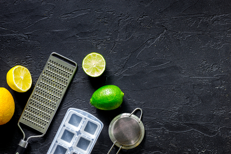Making lemonade. Cookware and fruits on black stone background top view.