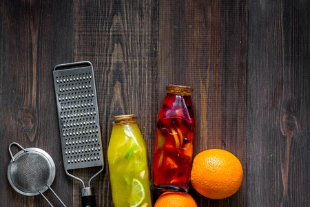 Making lemonade. Cookware, fruits and bottle of lemonade on wooden table background top view.