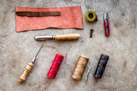 Leather workshop. Tanners tools on grey stone background top view