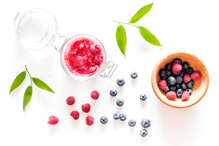 Raspberry jam in glass jar and frash berries bluberry on white background top view Stock Photo