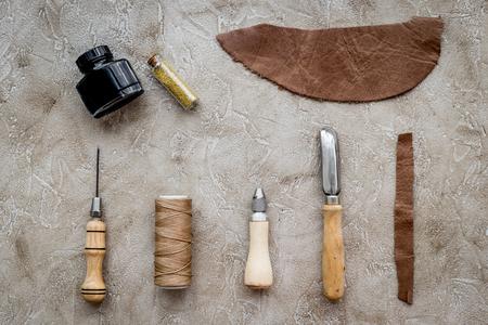 회색 돌 배경 상단 가죽 모형에 가죽 공예 도구 세트