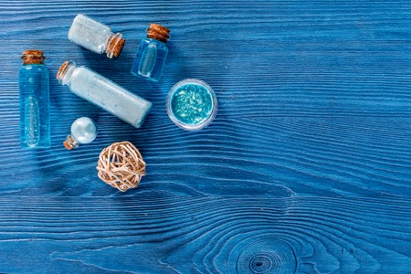 Spa set with sea salt, blue clay and lotion on blue wooden table background top view copyspace Banco de Imagens