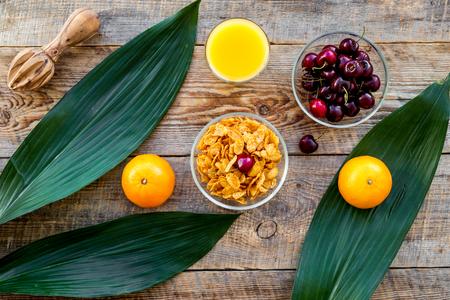 Summer fruity breakfast. Muesli, oranges, cherry on wooden table background top view Banco de Imagens