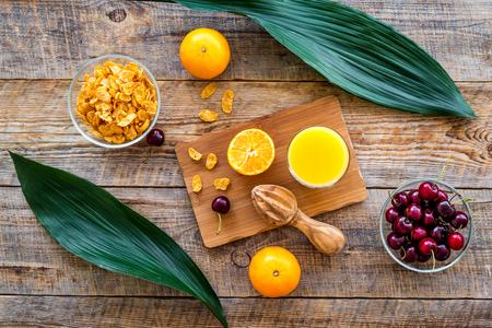 Vegetarian summer breakfast. Oranges, cherry and muesli on wooden table background top view Banco de Imagens