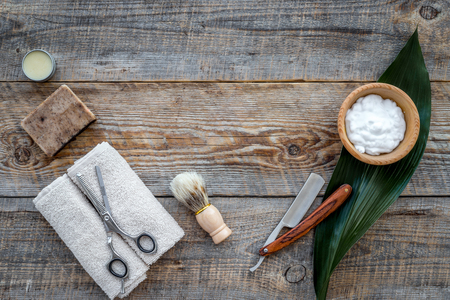 barbershop: Barber workplace. Shaving brush, razor, foam, sciccors on wooden table background top view copyspace