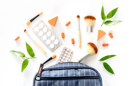 Beauty bag with cosmetics, contraceptives and pills on white table background top view