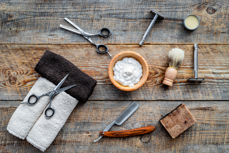 Barbershop. Mens shaving and haircut. Brush, razor, foam, sciccors on wooden table background top view Фото со стока