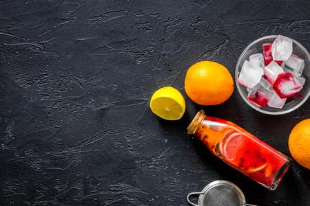 Botella de limonada fresca, frutas y cubitos de hielo en piedra negra fondo vista superior copyspace Foto de archivo - 82866596