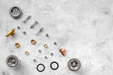 Sink drain parts and plumbing tools pattern on grey stone background top view copyspace Фото со стока