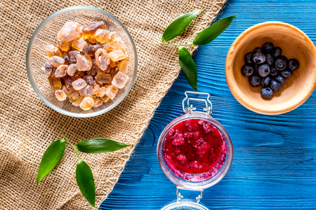 Homemade jam. Berries and sugar on blue wooden background top view copyspace