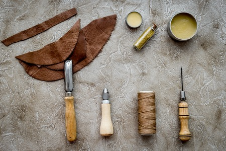 Leather craft. Tanners tools on grey stone background top view