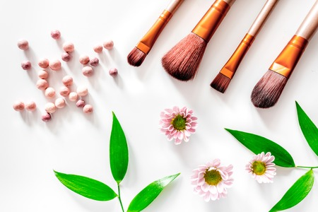 Make up brushes set and blush on white table background top view