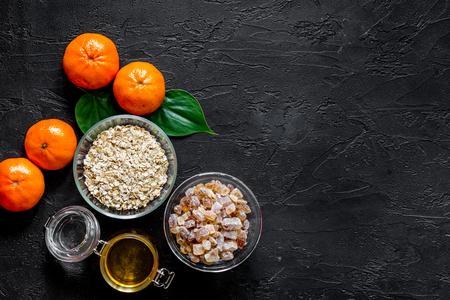 Preparing healthy breakfast. Porridge with oranges and honey on black stone table top view Banco de Imagens