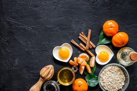 Preparing healthy breakfast. Porridge with oranges, cinnamon and honey on black stone table top view Banco de Imagens