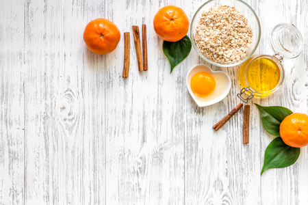 Preparing healthy breakfast. Cereals with oranges and honey on light wooden table top view copyspace