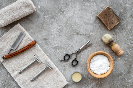 barbershop: Accessories for shaving. Shaving brush, razor, foam on grey stone table background top view.