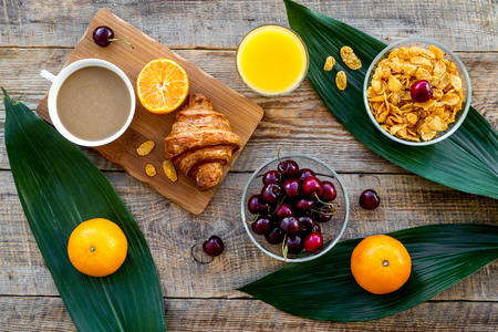 French breakfast. Fresh croissant, coffee, muesli, oranges on wooden table background top view