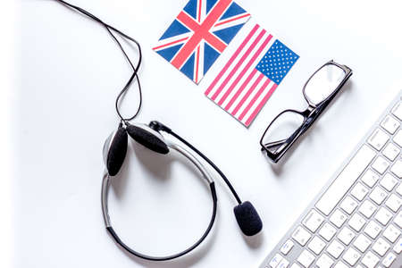 Self-education. Learning languages online. Headphones and keyboard on white table background top view. Stock Photo