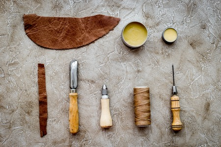 Set of leather craft tools on grey stone background top view.