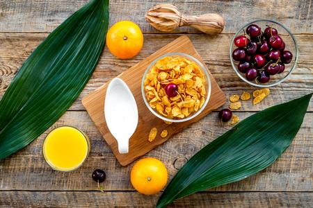 Summer fruity breakfast. Muesli, oranges, cherry on wooden table background top view.