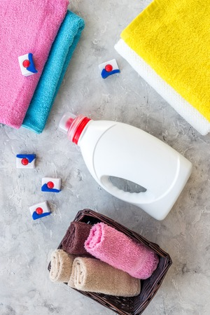 Wash clothes. Clean towel and detergent on grey stone background top view Stock Photo - 82928360