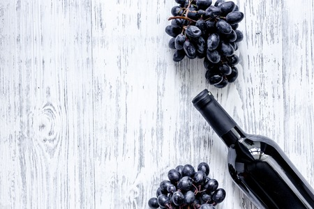 Bottle of wine and grape on light wooden table background top view copyspace