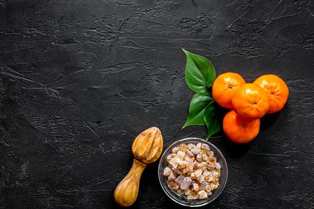 Ingredients for light summer dessert. Oranges and sugar on black background top view.