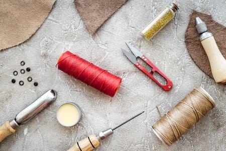 Leather crafting tools on grey stone background top view. Zdjęcie Seryjne