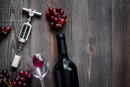 開いているワイン。ボトルとコルク栓抜き暗い木製のテーブル背景に平面図です。 写真素材