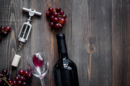 Open wijn. Fles en kurkentrekker op donkere houten tafel achtergrond bovenaanzicht.