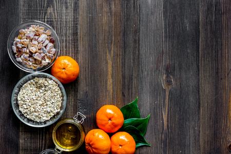 Sweet summer breakfast. Oatmeal, oranges, honey, sugar on wooden table background top view. Banco de Imagens