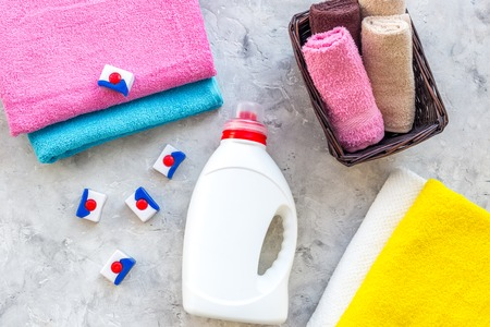 Wash clothes. Clean towel and detergent on grey stone background top view. Stock Photo - 83066941